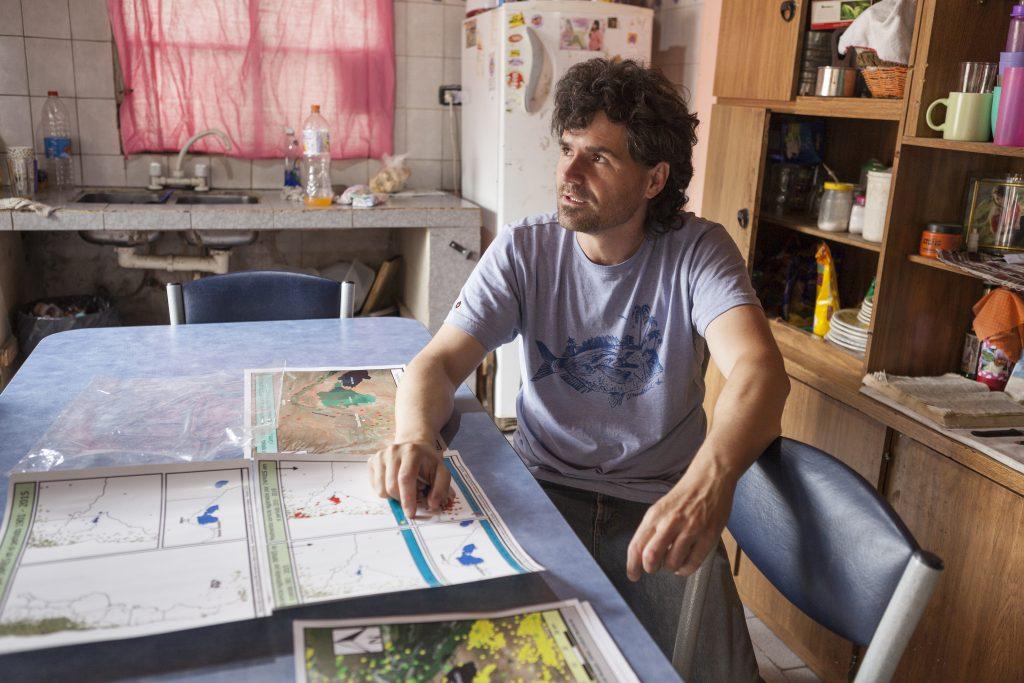 imagen de hombre sentado mirando un mapa de vaca muerta